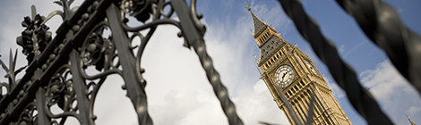 The iconic Big Ben tower, symbol of UK government, captured between the bars of the Houses of Parliament.